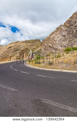 Turning empty road and warning sign beware of falling rocks protection barrier