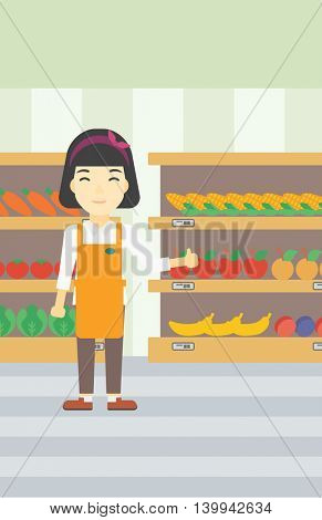 An asian young female supermarket worker showing thumb up on the background of shelves with vegetables and fruits in supermarket. Vector flat design illustration. Vertical layout.