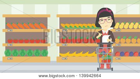 An asian thoughtful woman standing at the supermarket with supermarket trolley full with products and holding a shopping list in hands. Vector flat design illustration. Horizontal layout.