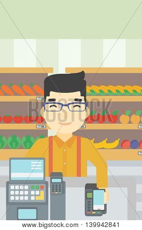 An asian young man paying wireless with his smartphone at the supermarket checkout . Male customer making payment for purchase with smartphone. Vector flat design illustration. Vertical layout.