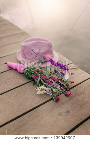on a wooden bridge pink hat and bouquet of flowers