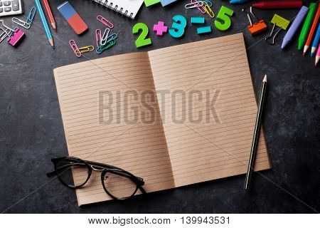Notepads and supplies over chalk board. Back to school concept with copy space