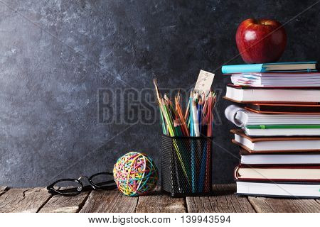 Notepads, supplies and glasses in front of chalk board. Back to school concept with copy space
