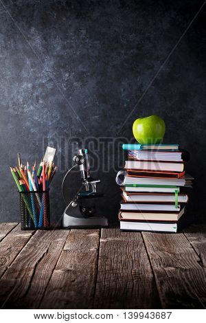 Notepads, supplies and apple in front of chalk board. Back to school concept with copy space