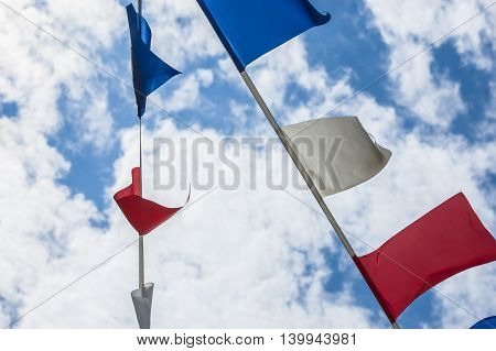 Colorful flags on blue sky with clouds