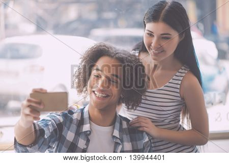 Our portrait. Smiling and positive young couple posing and
