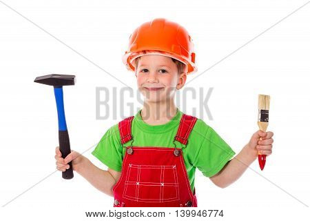Little builder in red coveralls and helmet with paintbrush and hummer, isolated on white