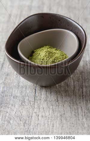 Dry Matcha Tea In A Small Brown Plate. Grey Wood Background