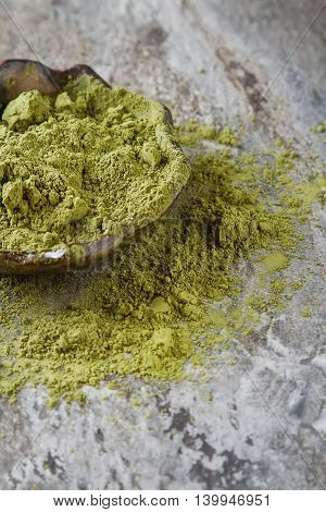 Dry Matcha Tea In A Small Brown Plate. Dark Ceramic Background