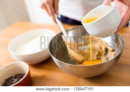 Woman mixing the paste with adding egg