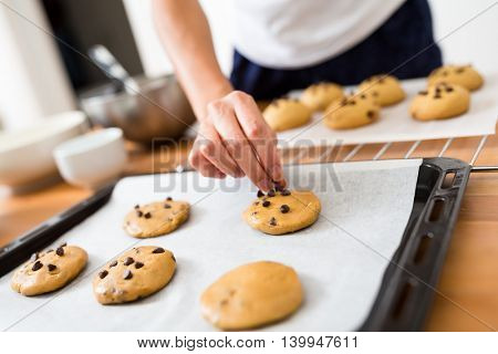 Woman adding chocolate on the cookies