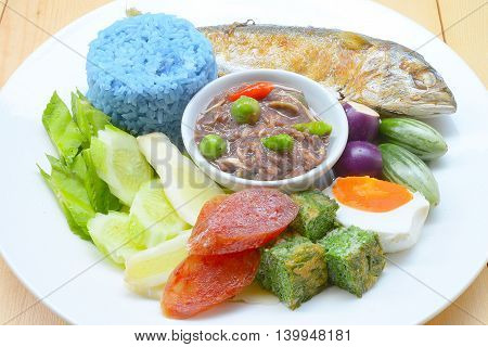 Rice with fried mackerel, boiled egg, shrimp paste, chilli sauce and vegetables, original Thai food.