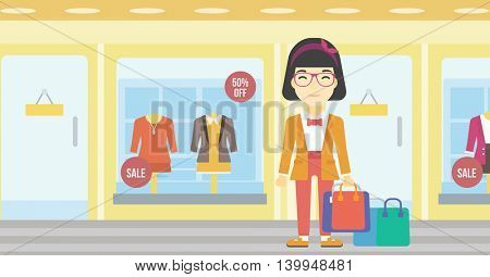 An asian woman holding shopping bags on the background of boutique window with dressed mannequins. Happy woman carrying shopping bags. Vector flat design illustration. Horizontal layout.