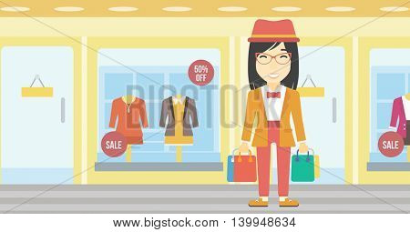 An asian woman holding shopping bags on the background of boutique window with dressed mannequins. Happy young woman carrying shopping bags. Vector flat design illustration. Horizontal layout.