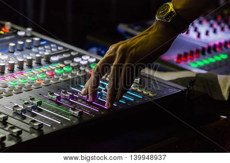 Audio mixer mixing board fader and knobs with selective focus on buttons Music mixing console with backlit buttons