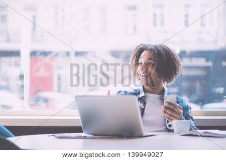 Wow. Happy and cheerful young man using mobile phone and laptop while being in a cafe
