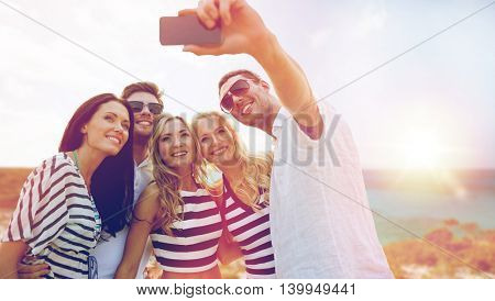 summer holidays, travel, tourism, technology and people concept - group of smiling friends with smartphone photographing and taking selfie over exotic beach background