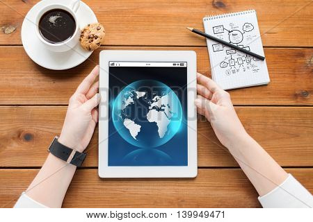 business, international, technology and people concept - close up of woman with earth globe on tablet pc computer screen, notebook and coffee on wooden table