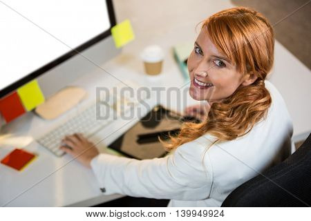 High angle portrait of pretty businesswoman working at desk in office