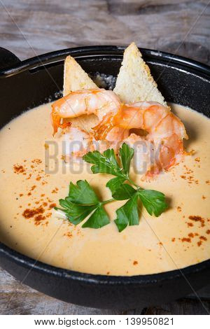 Tom Yum thai traditional soup with shrimps served in a metal bowl