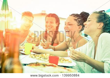 Friends having fun eating pizza at sunset on beach bar restaurant - Cheerful teenagers laughing at dinner party on summer vacation - Concept of joyful meal together