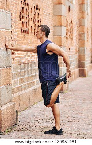 Jogger standing at brick wall and stretching leg
