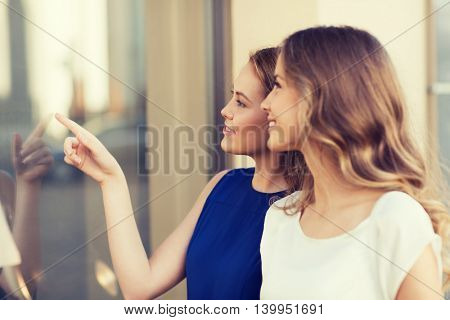 sale, shopping, consumerism and people concept - happy young women pointing finger to shop window outdoors
