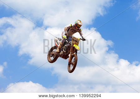 Wingate, Israel - July 23, 2016: Motocross rider and bike clearing a tabletop jump during the final heat of the race.