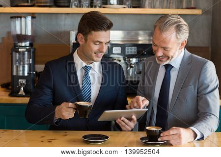 Businessmen using digital tablet while having coffee in café