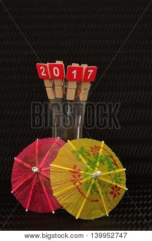 2017 spelled with red blocks displayed on the rim of a shooter glass with a red and yellow  cocktail umbrella on a black background