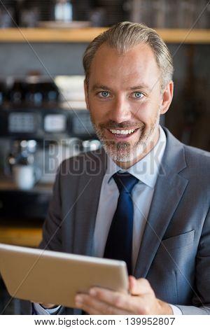 Portrait of happy businessman using digital tablet in café