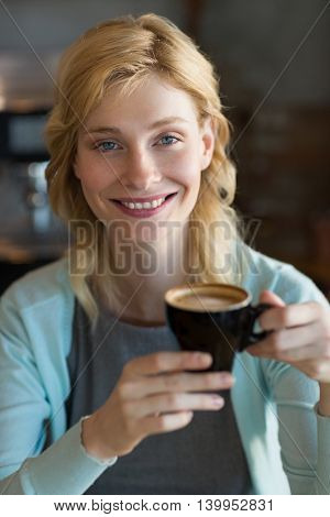 Close-up of beautiful woman having coffee in café