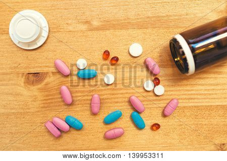Colorful medical tablets and pills scattered on the desk top view