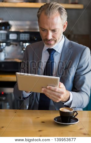 Close-up of businessman using digital tablet while having coffee in café
