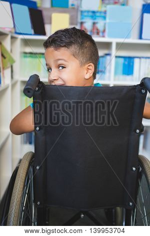 Portrait of disabled schoolboy in library at school