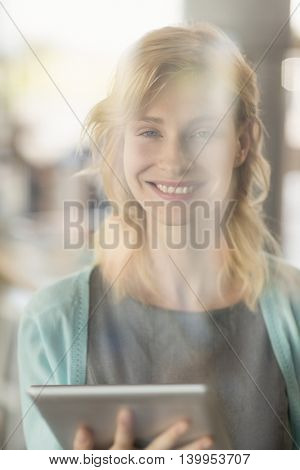 Portrait of beautiful woman using digital tablet in café