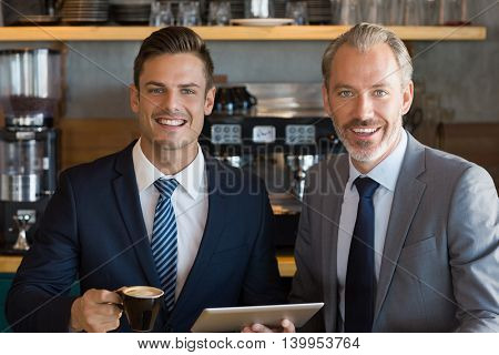 Portrait of businessmen using digital tablet while having coffee in café