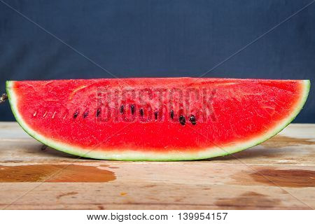 Watermelon - delicious fruit. Slices of red watermelon.   Slices of watermelon on a coconut on the wooden table.