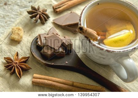 Pieces of chocolate, tea with lemon, cinnamon and anise