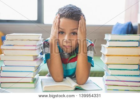 Portrait of schoolboy reading a book in library at school