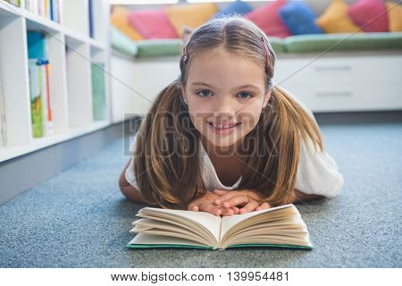 Portrait of schoolgirl lying on floor and reading a book in library at school