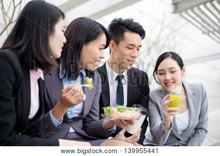 Group of business team having salad outside office