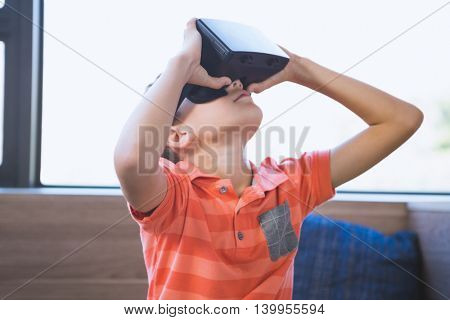 School boy in virtual reality glasses in library at school
