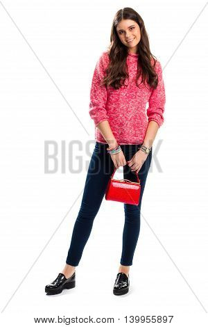 Lady with red bag smiling. Black shoes and pink pullover. Autumn outfit with glossy handbag. Trendy colorful accessories.