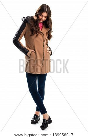 Woman in coat looks down. Pants and coat with inserts. Brand new autumn shoes. Apparel from top quality materials.
