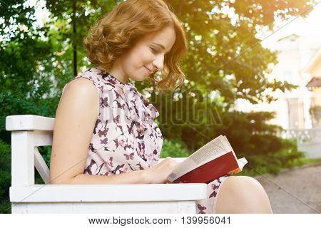 Beautiful young woman reading book on park bench on summer sunny day. Image with lens flare effect