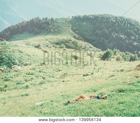 Traveler young woman resting on green meadow in summer mountains