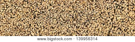 Large pile of wood logs make for a nice natural pattern or texture background in panorama format