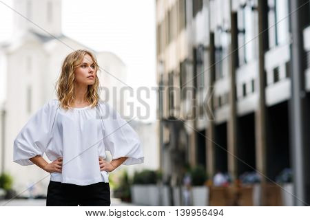 Blond woman standing outdoors and looking thoughtfully into distance