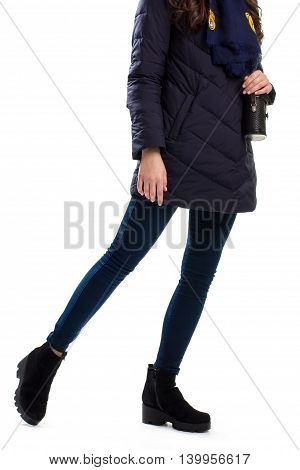 Lady wears navy down jacket. Black boots and skinny pants. Young model in winter apparel. Footwear with warm lining.